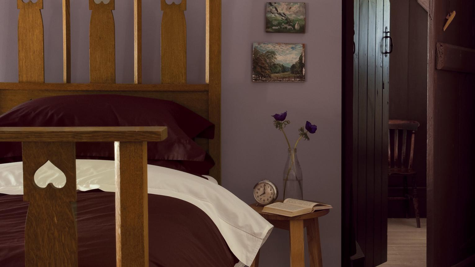 Purple walls bring warmth and nostalgia to this cosy bedroom.